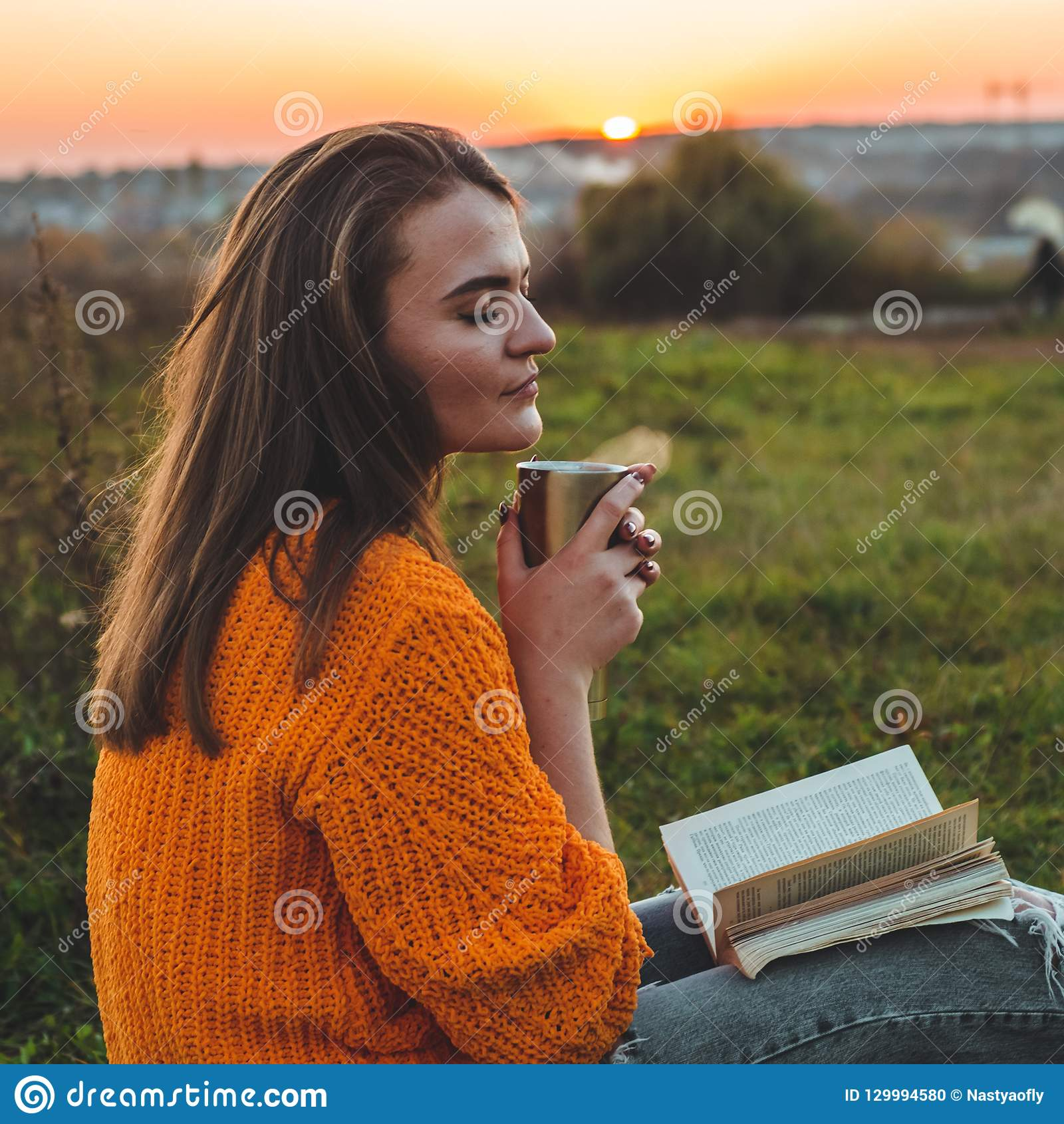 The concept of lifestyle outdoor recreation in autumn. Girl read books on plaid with a thermo cup. Autumn. Sunset. Cozy