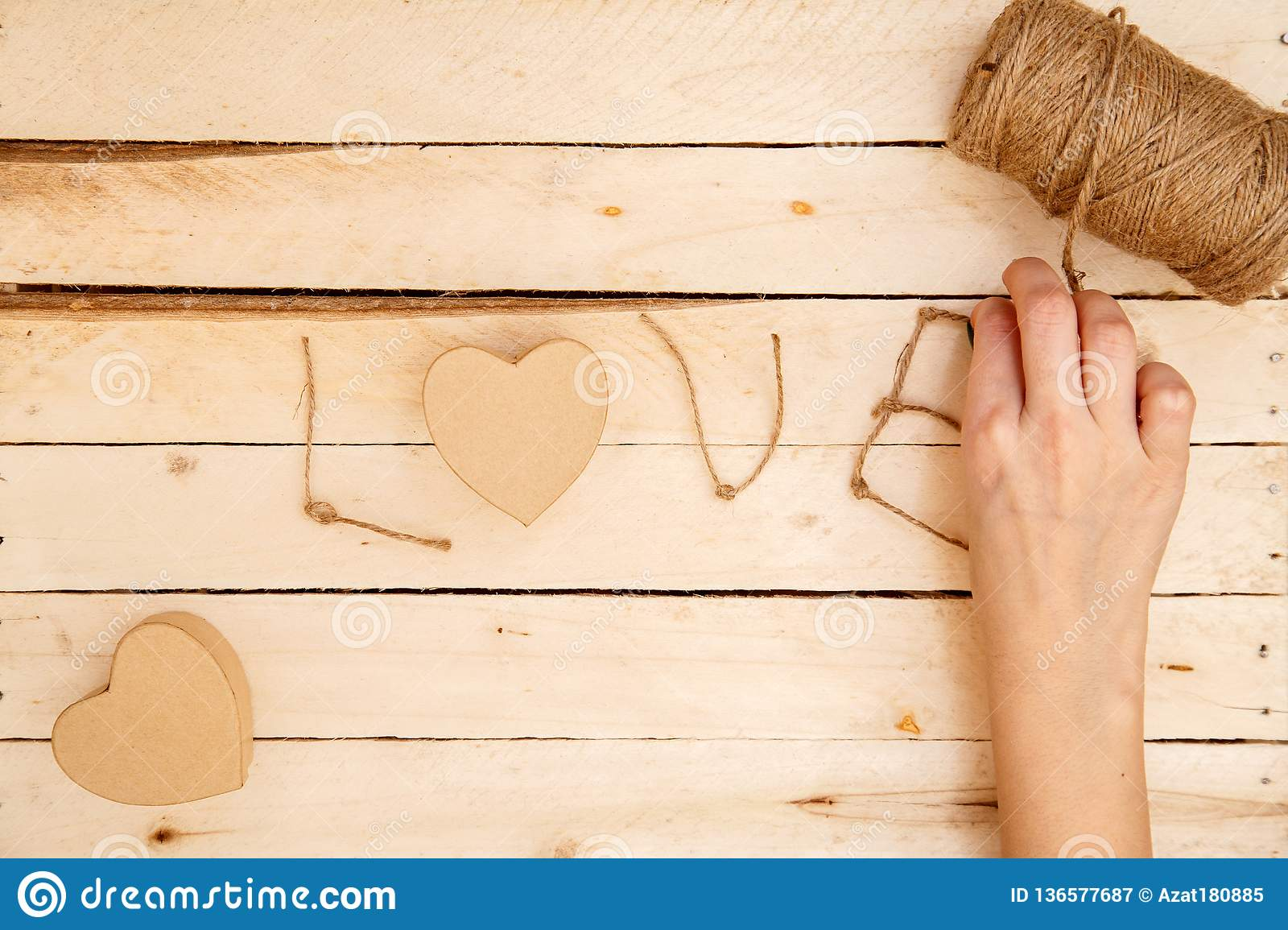 Concept for love stories and for Valentine`s Day. Female hands make boxes in the form of a heart and the inscription `love` from a