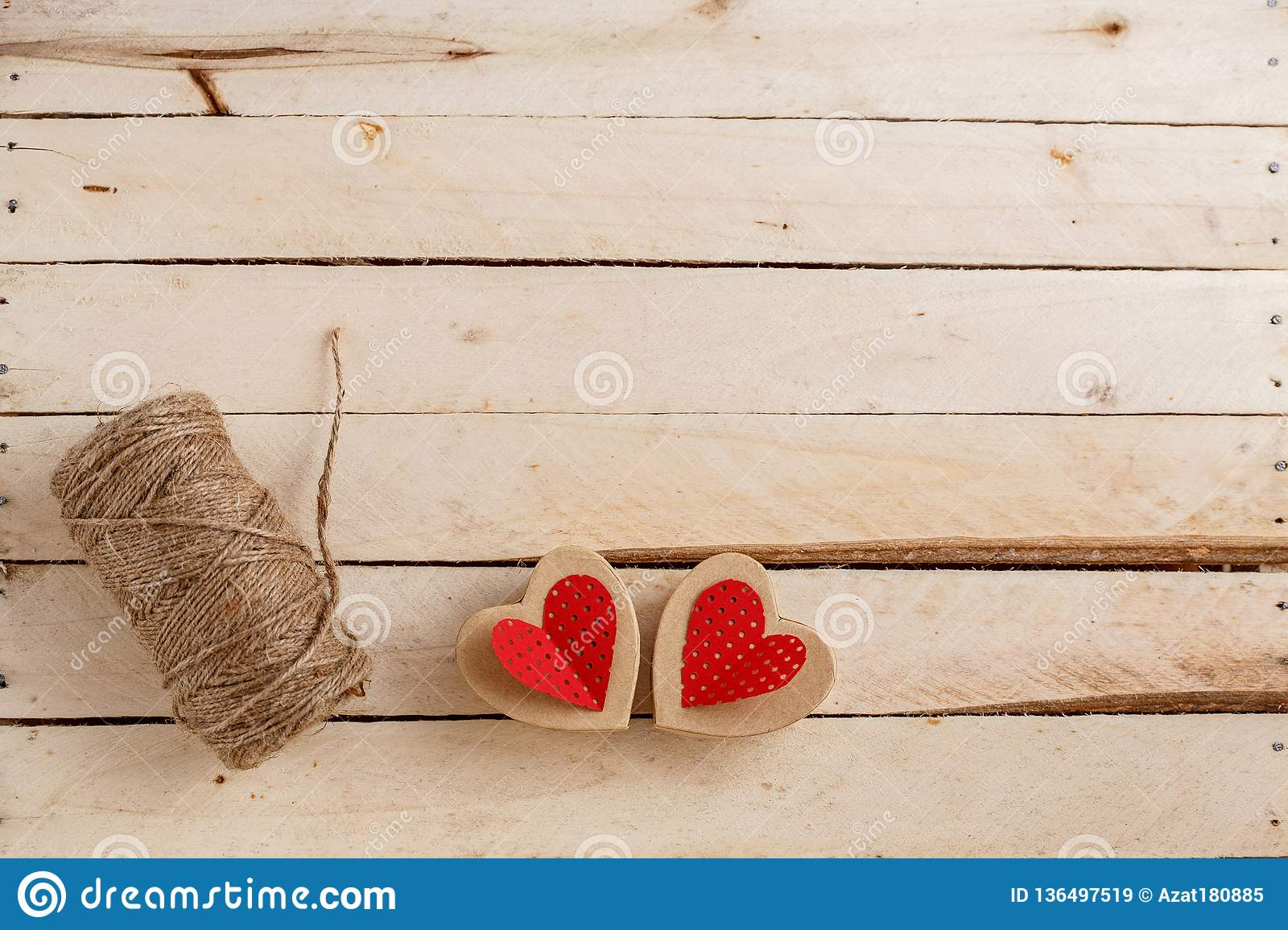 Concept for love stories and for Valentine`s Day. The string, the inscriptions from it and handmade cardboard hearts on a natural