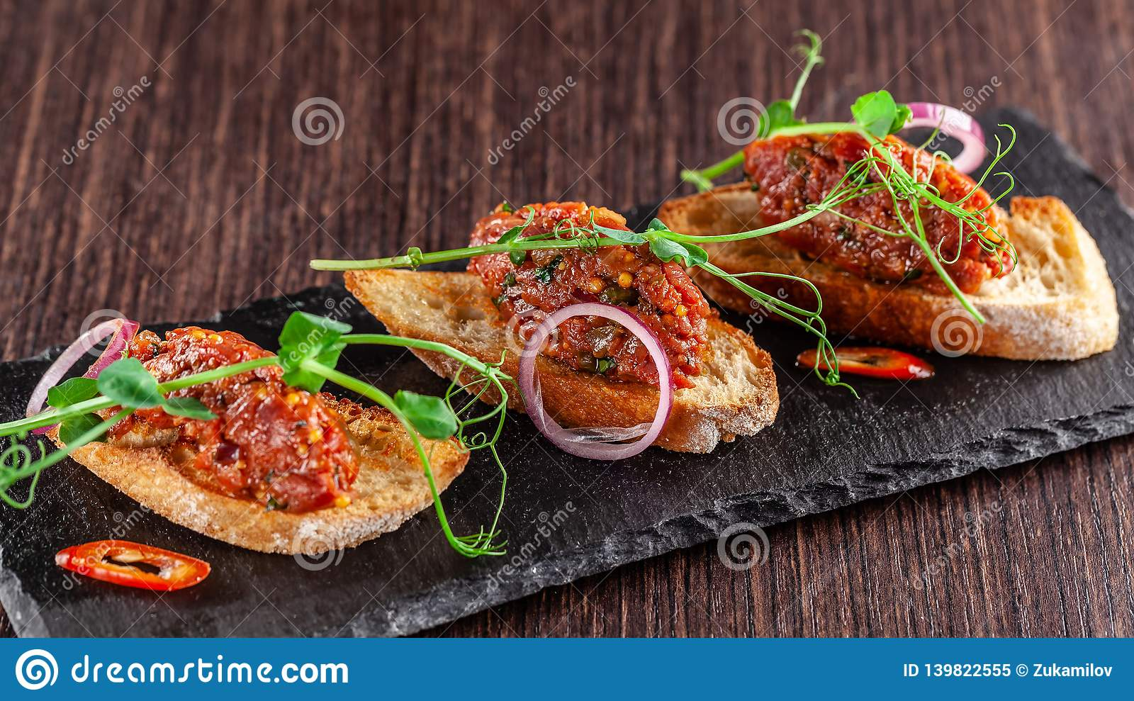 The concept of Mexican cuisine. Beef tartare with parsley, French mustard beans on baguette croutons. A dish in the restaurant