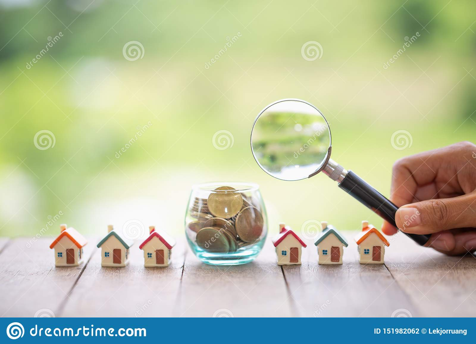 Concept of a mortgage, a coin, a model of a house and a magnifying glass, house and money. magnifying glass and coins,