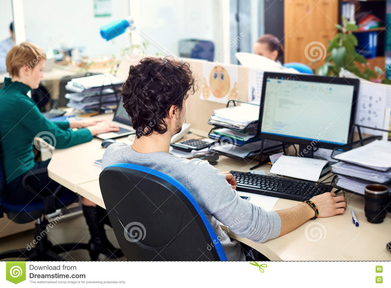 the concept of office work rear view man working at a comput stock