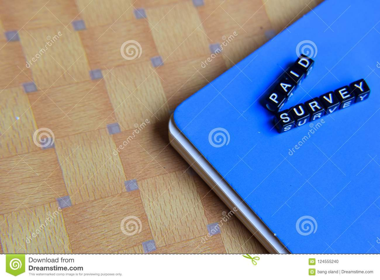 Concept of Paid Survey on wooden cubes with books in background