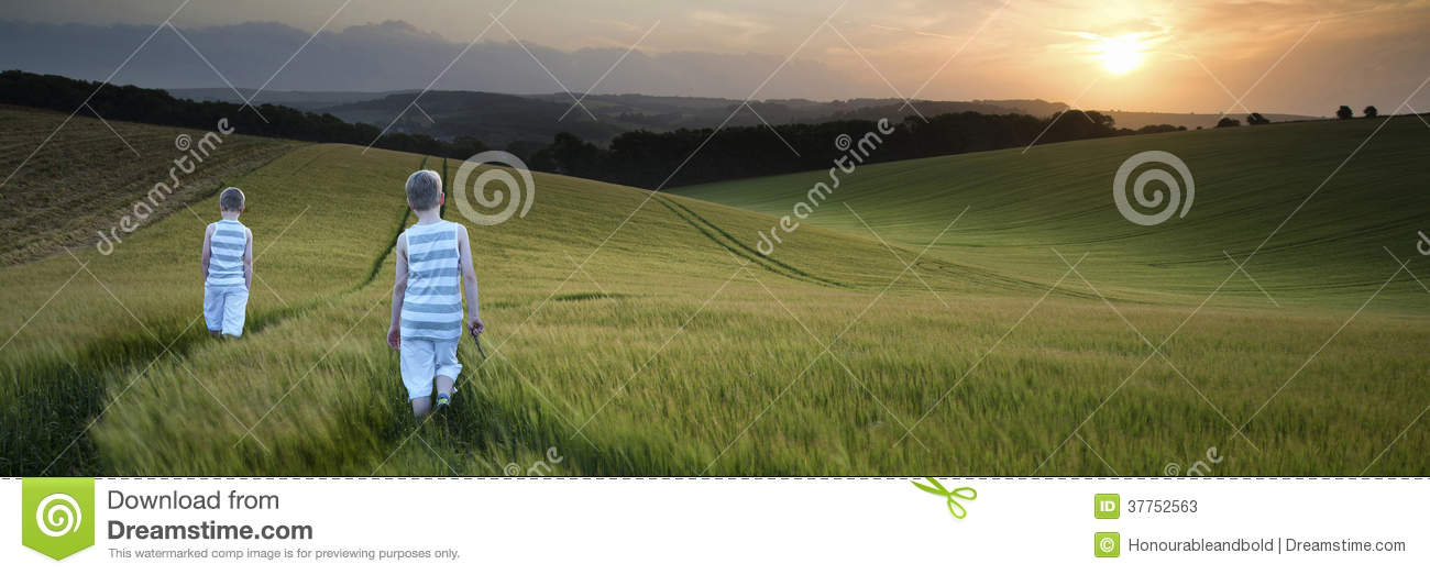 Concept panorama landscape young boys walking through field at s