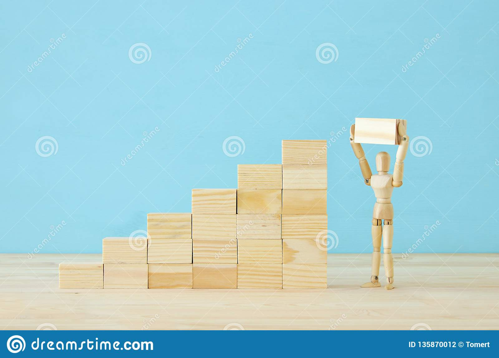 concept photo of obstacles overcoming, wooden dummy looking at a barrier and thinking about solution.