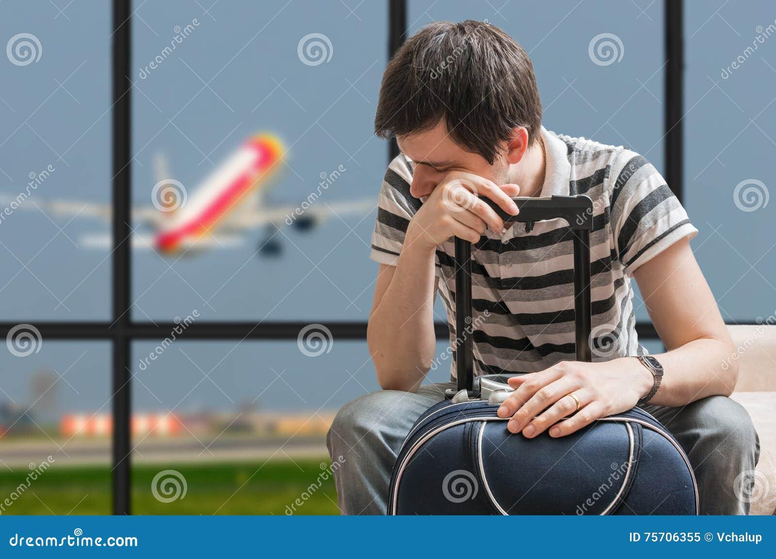 Concept retardé d avion Le passager fatigué s assied avec des bagages dans l aéroport