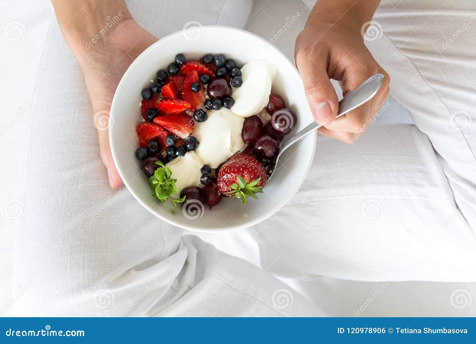 Concept sain de consommation Le ` s de femmes remet tenir la cuvette avec le fromage blanc avec de la crème, la fraise, la cerise