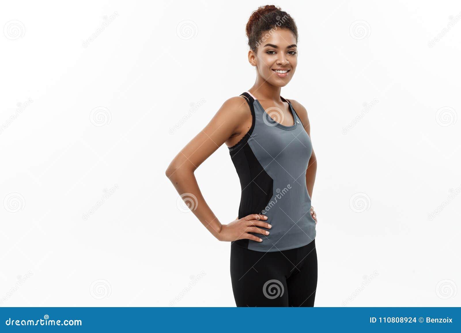 Concept sain et de forme physique - la belle dame africaine américaine dans la forme physique vêtx prêt pour la séance d entraîne