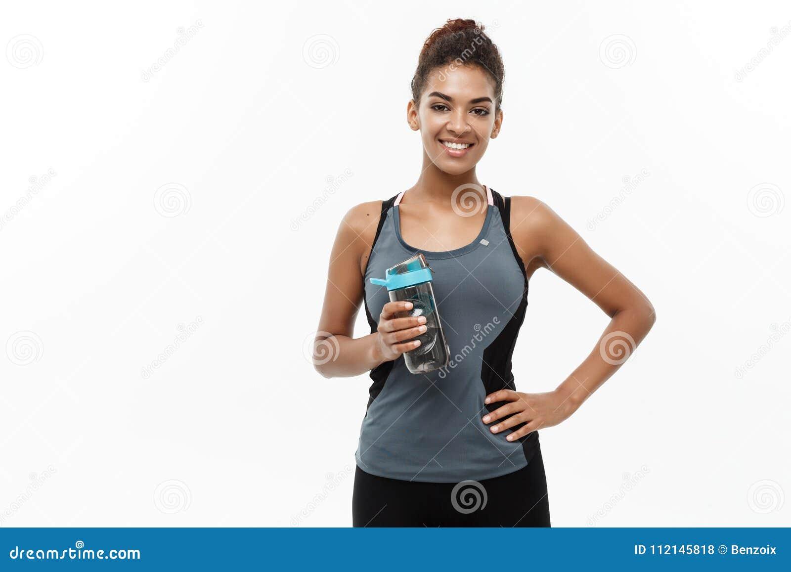 Concept sain et de forme physique - la belle fille d Afro-américain dans le sport vêtx tenir la bouteille d eau après séance d en
