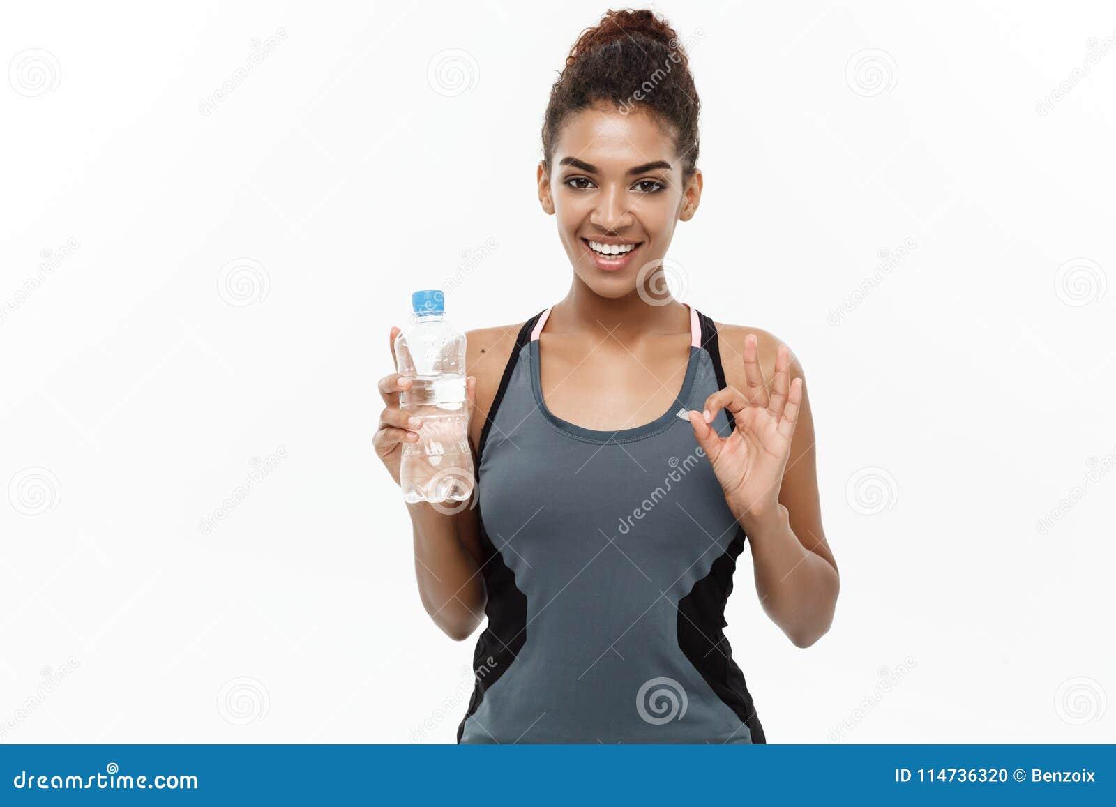 Concept sain et de forme physique - la belle fille d Afro-américain dans le sport vêtx tenir la bouteille d eau en plastique ensu