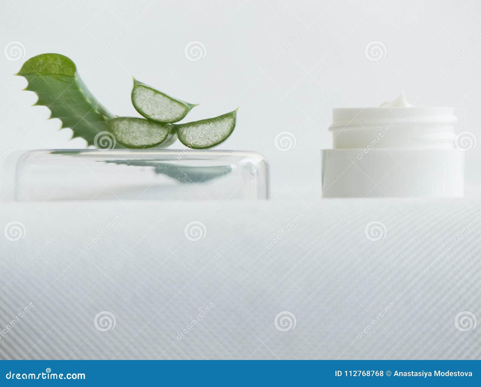 Close up aloe vera slices white cream jar