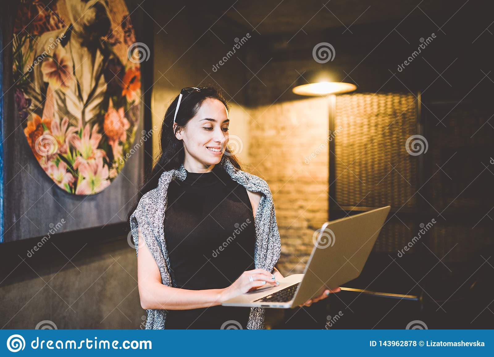 The concept of small business and technology. Young beautiful brunette businesswoman in black dress and gray sweater stands in