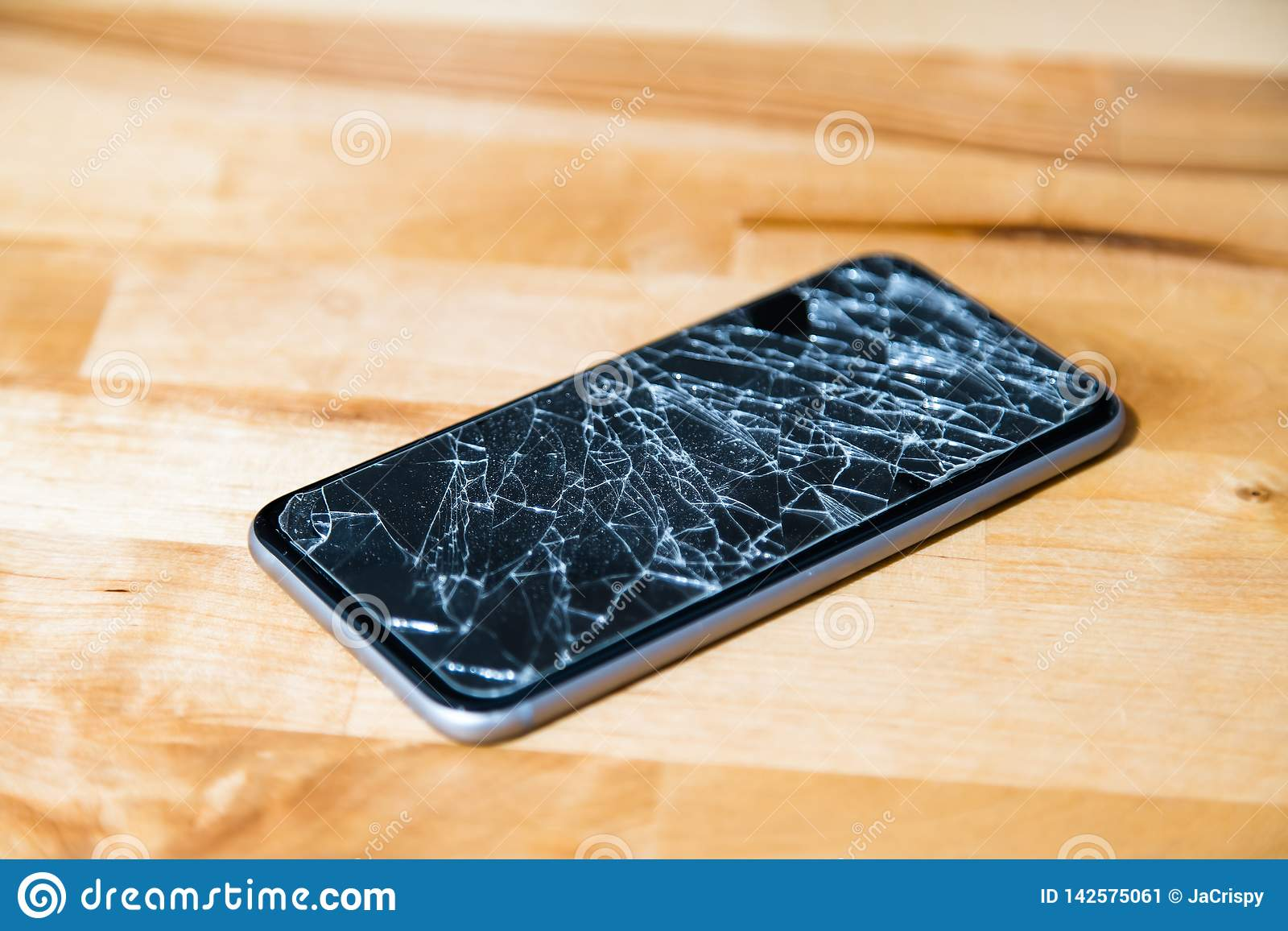 Concept of smart phone with broken screen. Top view on wooden desk background. Cracked, shattered lcd touch screen on modern