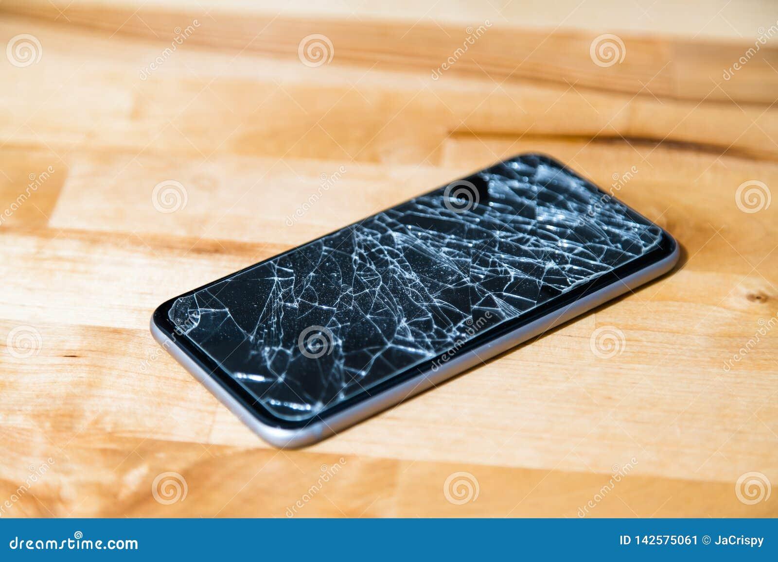 Concept smartphone met het gebroken scherm Hoogste mening over houten bureauachtergrond Gebarsten, verbrijzeld lcd touch screen o