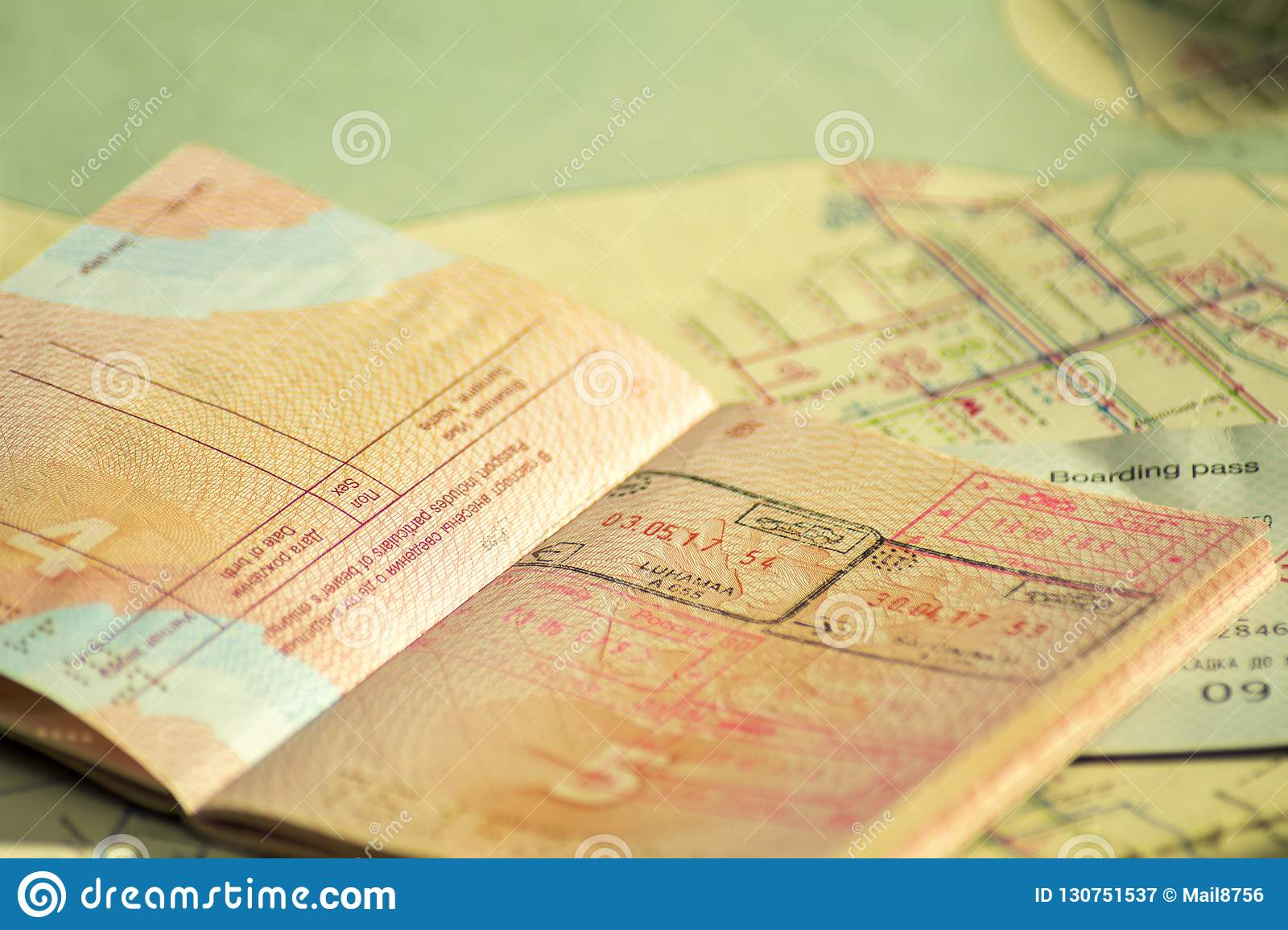 The concept of travel. Russian passport with visas. Passport and plane ticket is on the old map. Sunlight and shadow