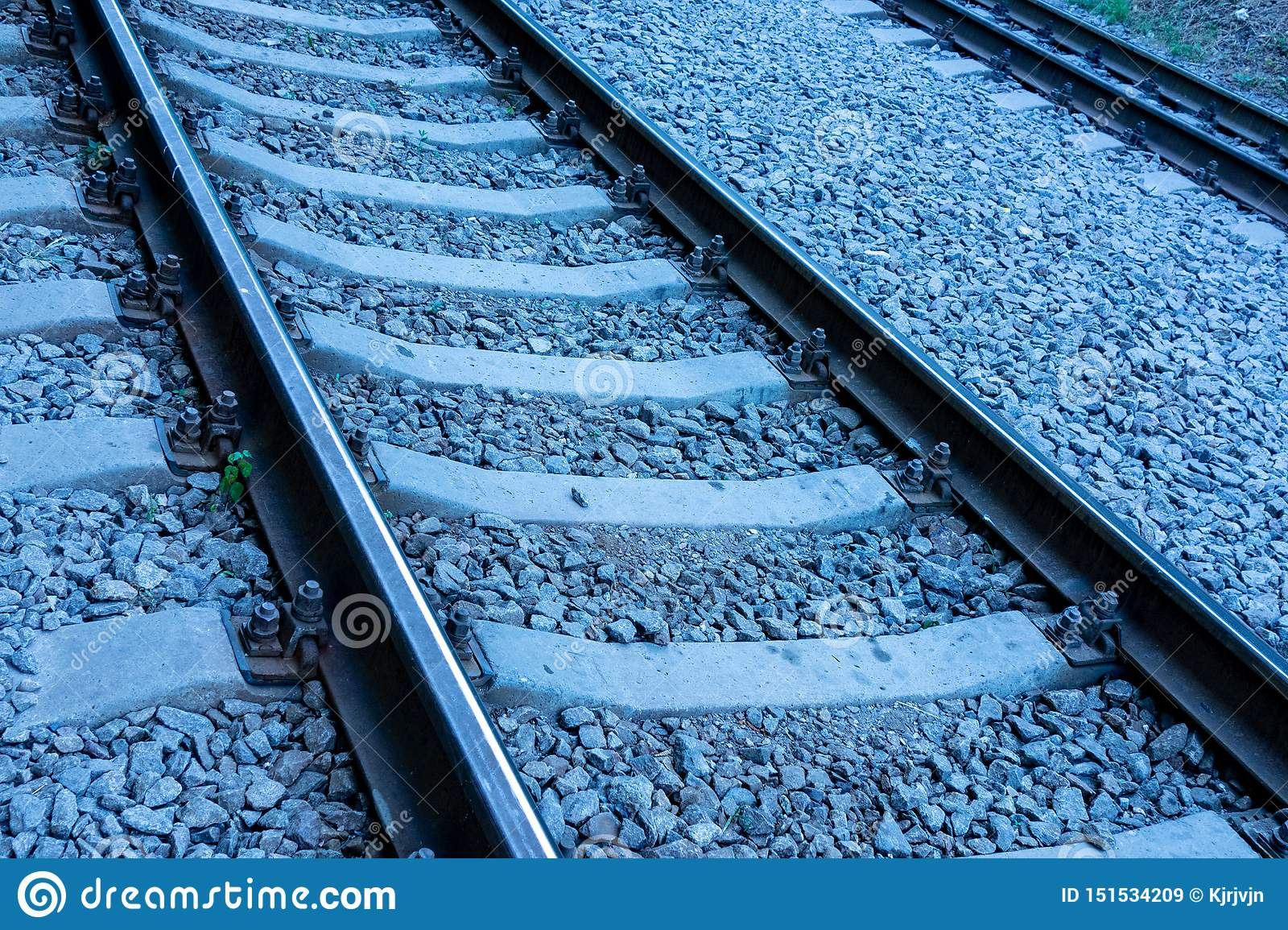 Concept of travel by train on railroads. Rails track is going upward in blue colored night or evening time. Cargo and passenger