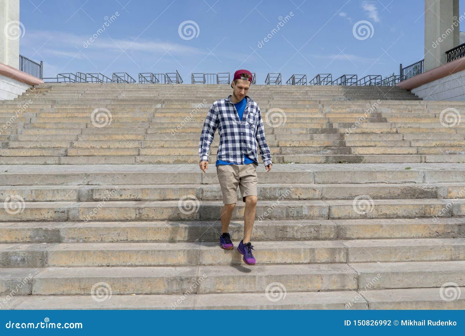 Concept urbain, promenade de jeune homme sur les escaliers dans la ville