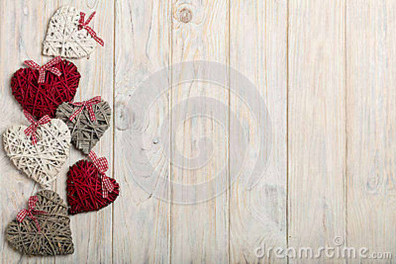 Concept Of Valentine s Day. Wicker hearts on wooden background w