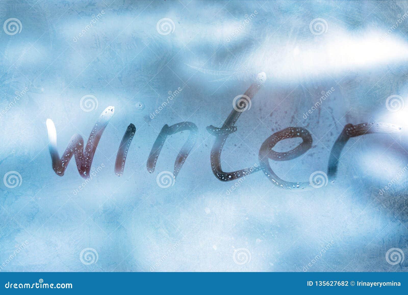 Concept van het de WINTER het koude weer De WINTER van het inschrijvingswoord op het glasvenster met bevroren patronen
