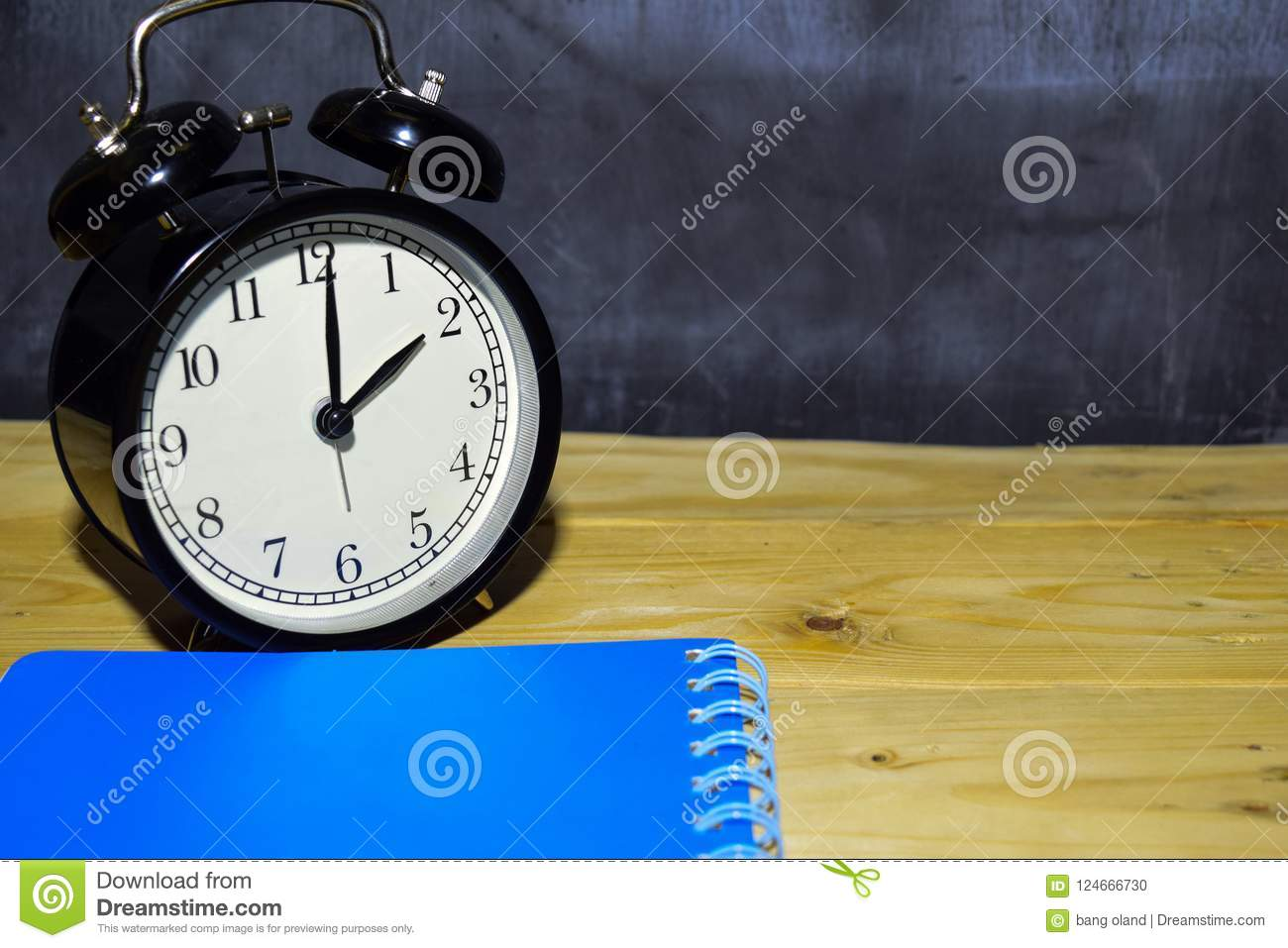 Concept vintage background black retro alarm clock on 14.00 pm or 02.00 am and blue book