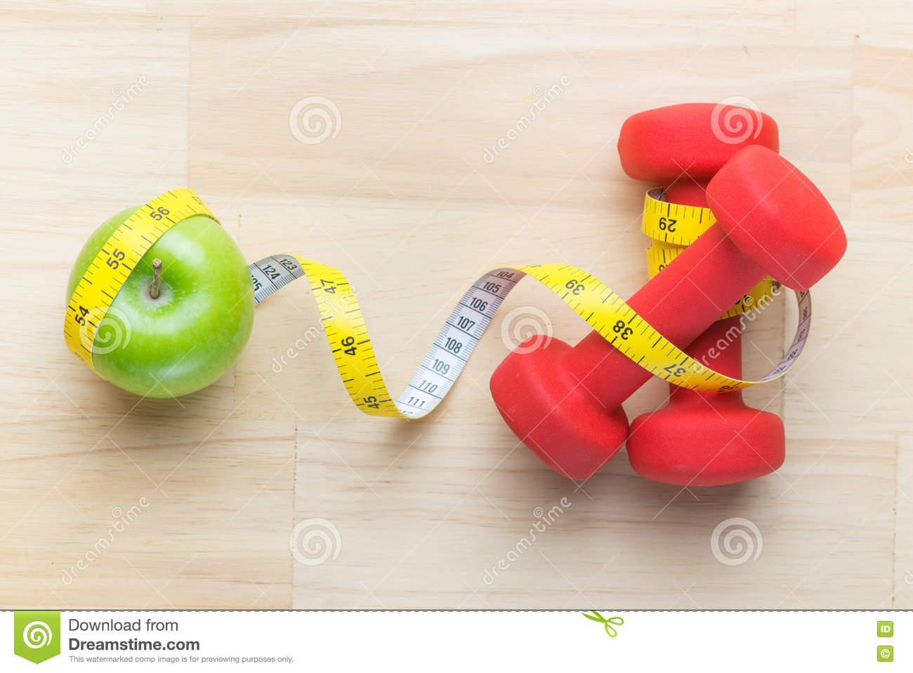 Fitness concept with dumbbell and apple royalty free stock