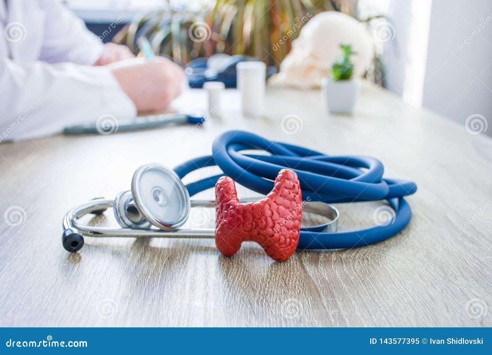 Conceptenfoto van diagnose en behandeling van schildklier In voorgrond is model van schildklier dichtbij stethoscoop op lijst in