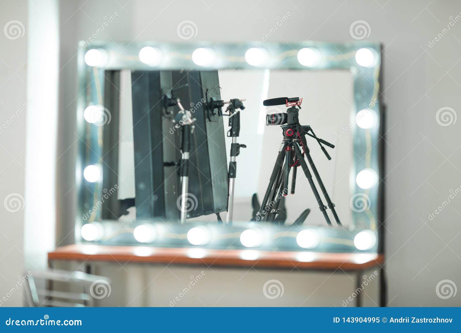 Conceptengesprek, digitale camera op een driepoot met een binnen microfoon in de studio op een witte achtergrond in de spiegelbez