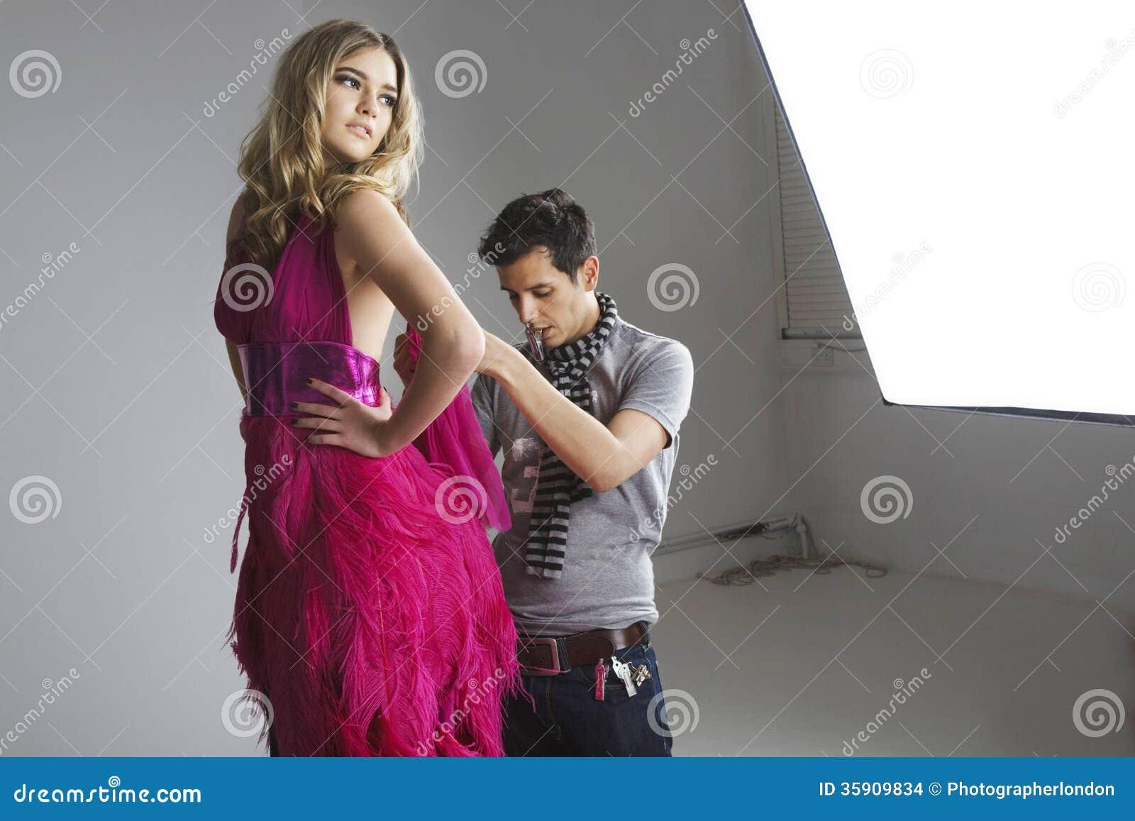 Concepteur ajustant la robe sur le mannequin dans le studio
