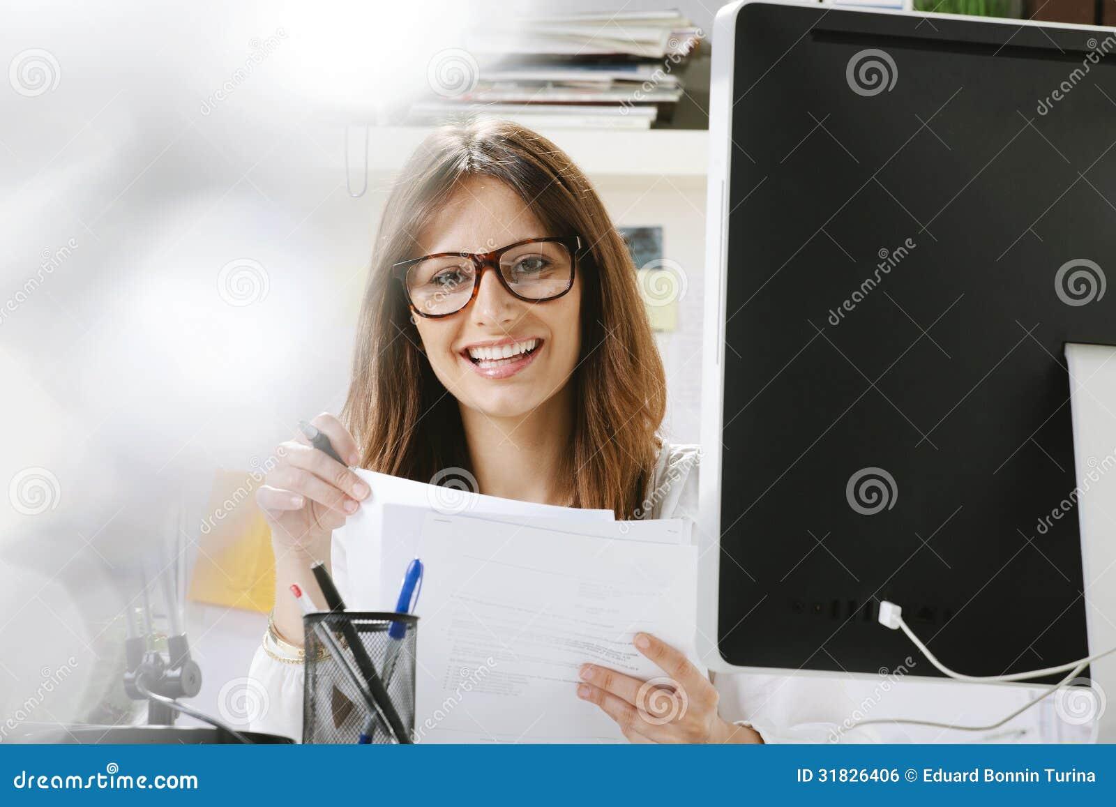Concepteur créatif de jeune femme avec des documents fonctionnant dans le bureau.