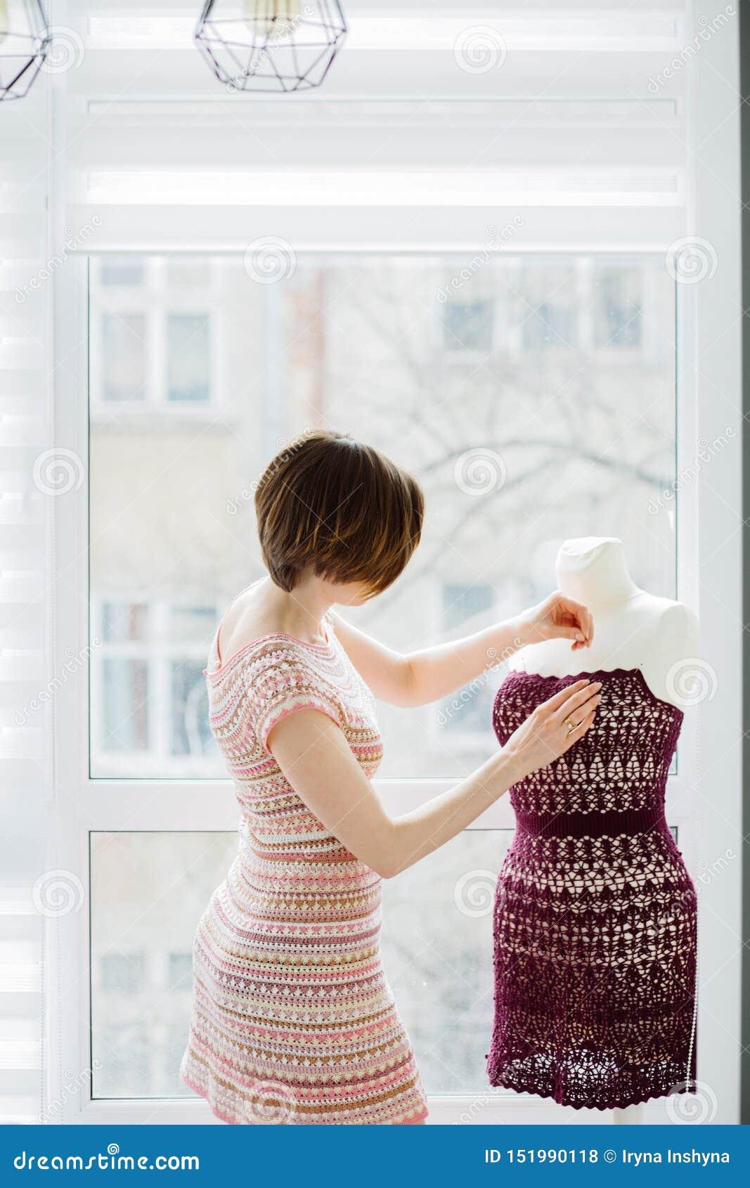 Concepteur féminin aux cheveux courts d habillement employant le simulacre de robe au mode de vie intérieur et indépendant à la m