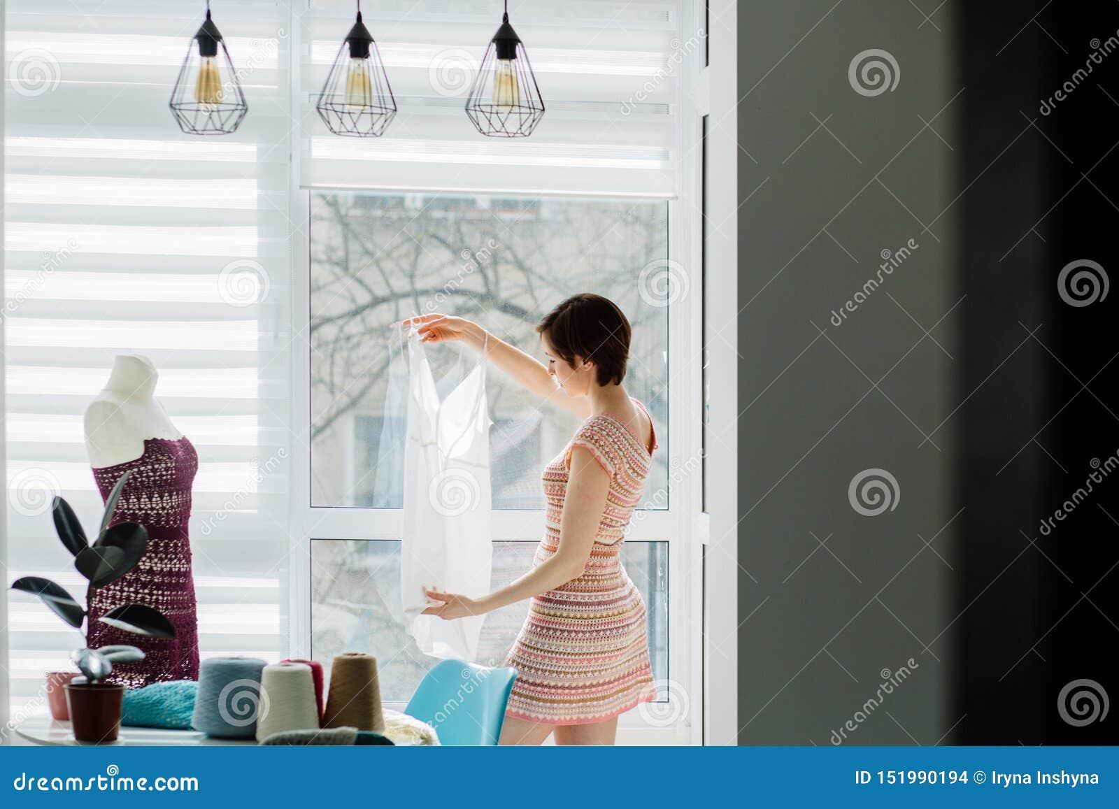 Concepteur féminin travaillant avec la robe tricotée dans le studio confortable intérieur, indépendant, mode de vie, concept d in