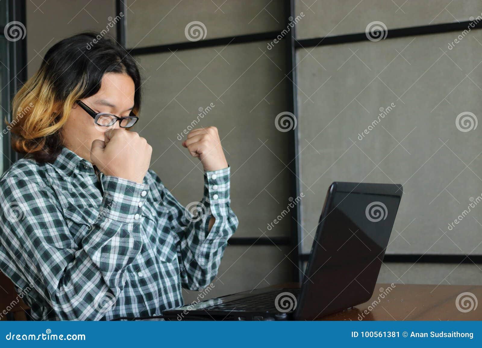 Concepto acertado del asunto Trabajador asiático confiado que aumenta los brazos y que siente feliz contra el suyo el trabajo en