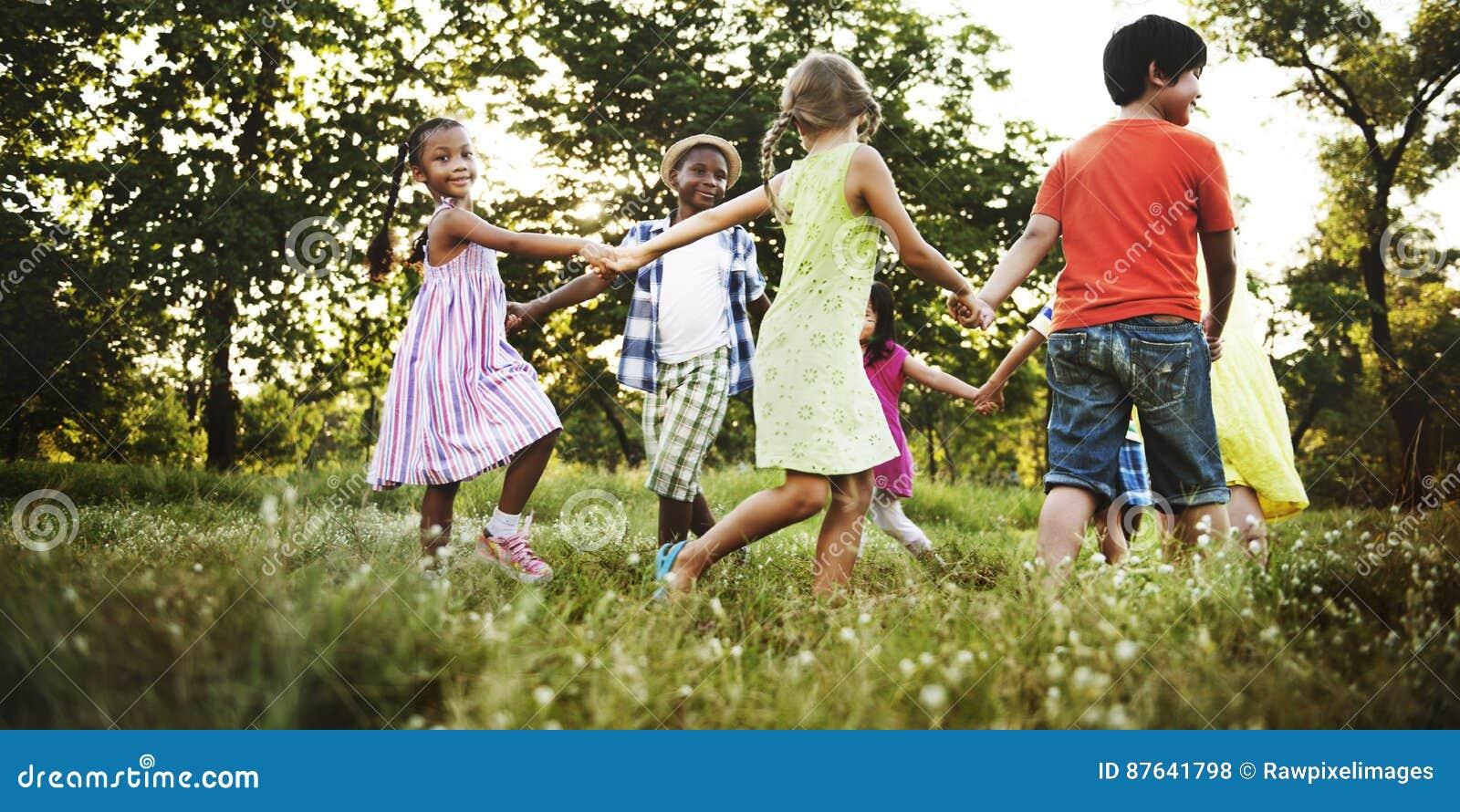 Concepto alegre de la naturaleza juguetona de las muchachas de los muchachos de los amigos del niño
