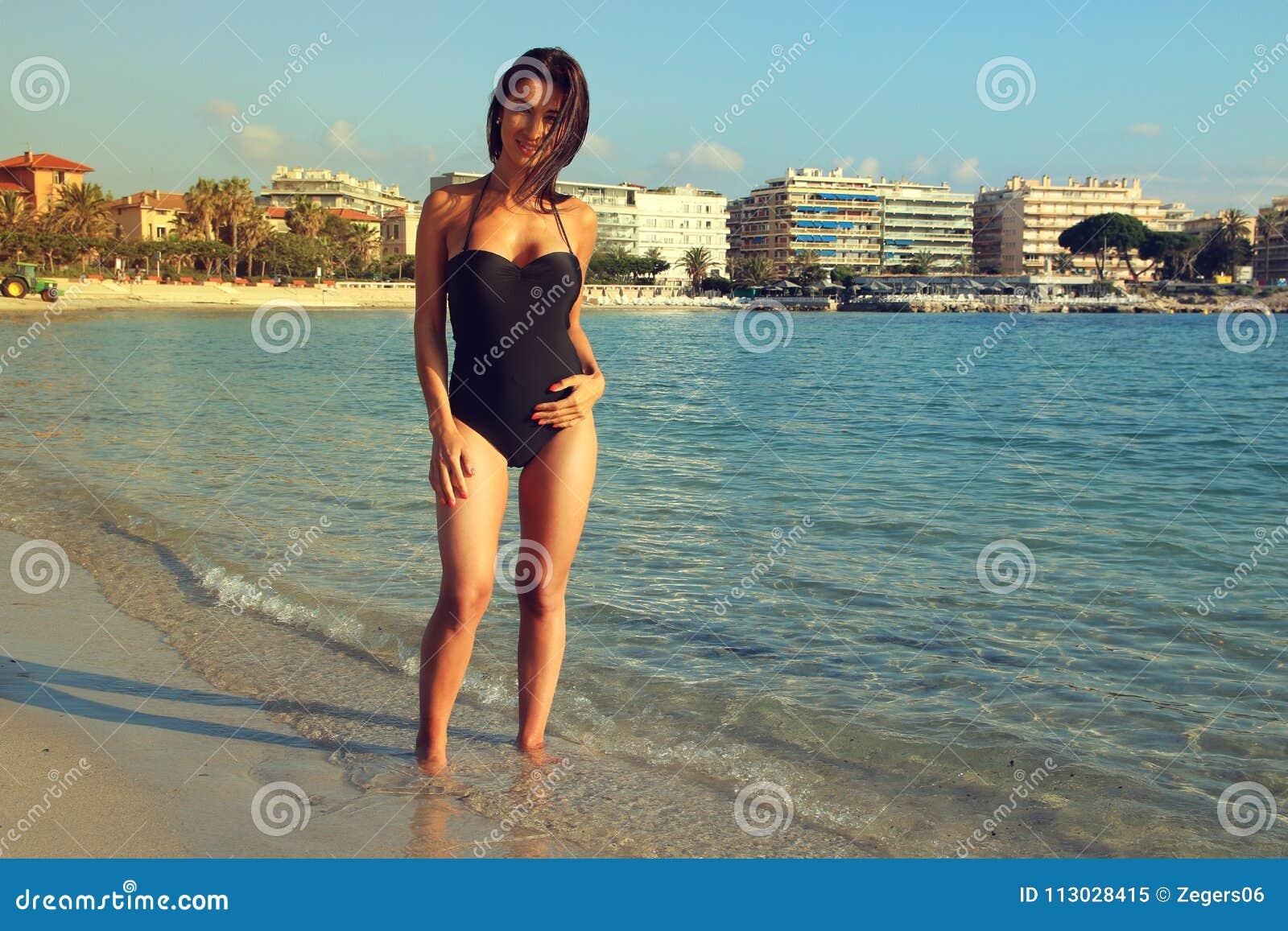 Concepto atractivo de la muchacha en traje de baño Mujer hermosa que lleva un traje de baño que juega en la playa
