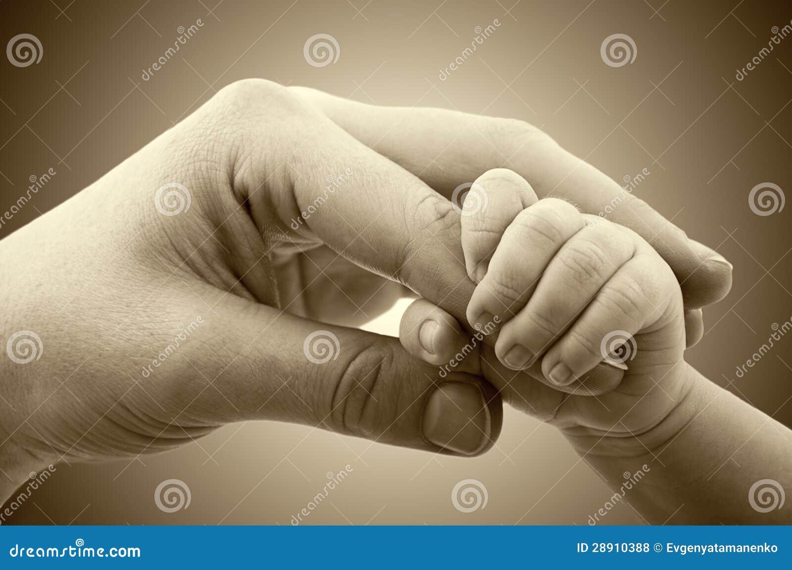 Concepto de amor y de familia. manos de la madre y del bebé