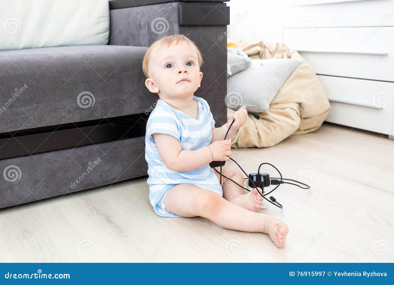 Concepto de bebé en peligro Bebé que se sienta en piso solamente y p