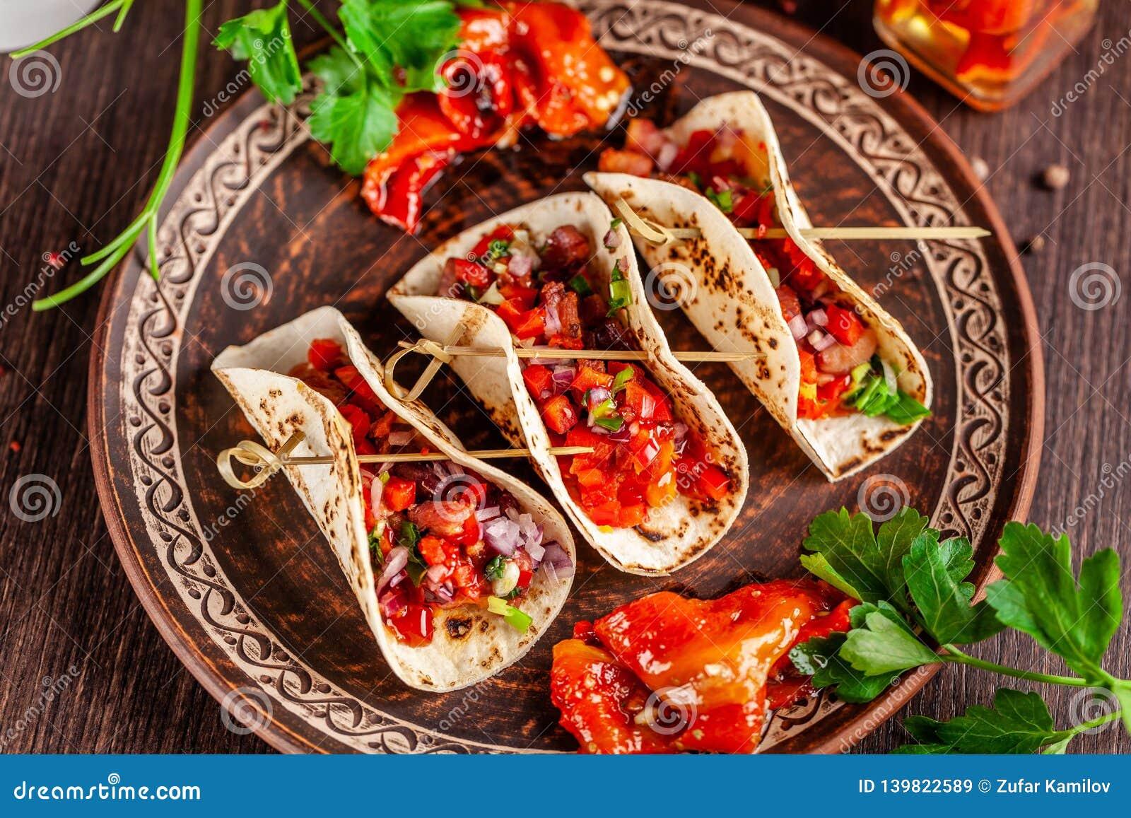 Concepto de cocina mexicana Tacos mexicanos del aperitivo con las verduras, habas, paprika, pimientas de chiles en el pan ácimo f