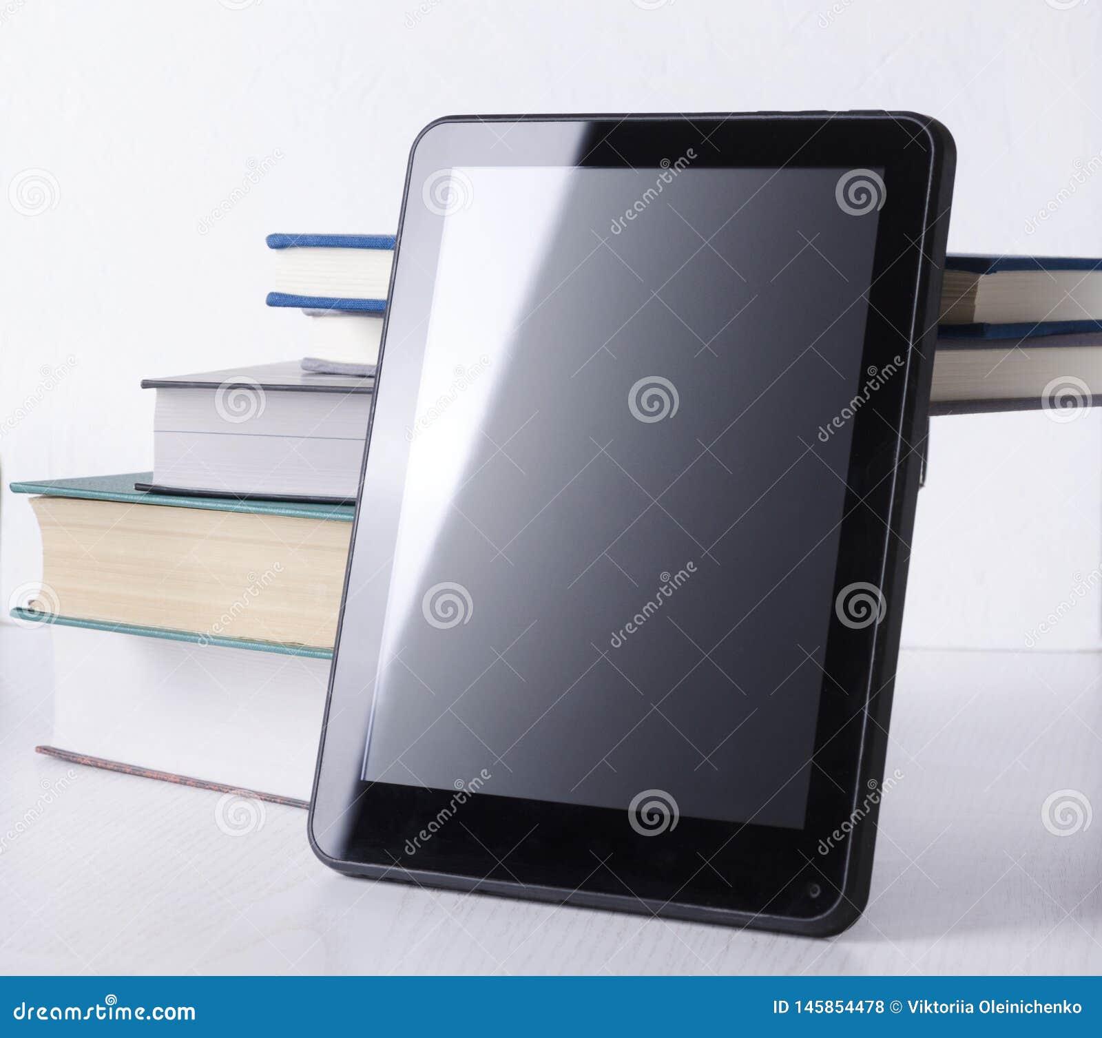 Concepto de educaci?n en l?nea Pila de libros y de pantalla en blanco de la tableta