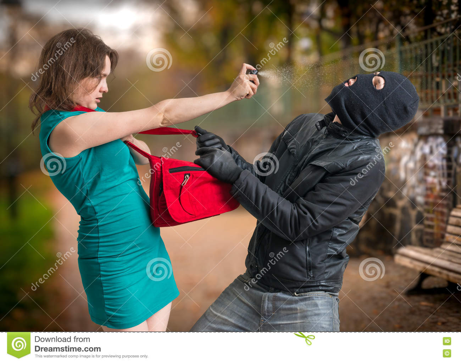 Concepto de la autodefensa Al hombre en pasamontañas atacó a la mujer joven está utilizando el spray de pimienta