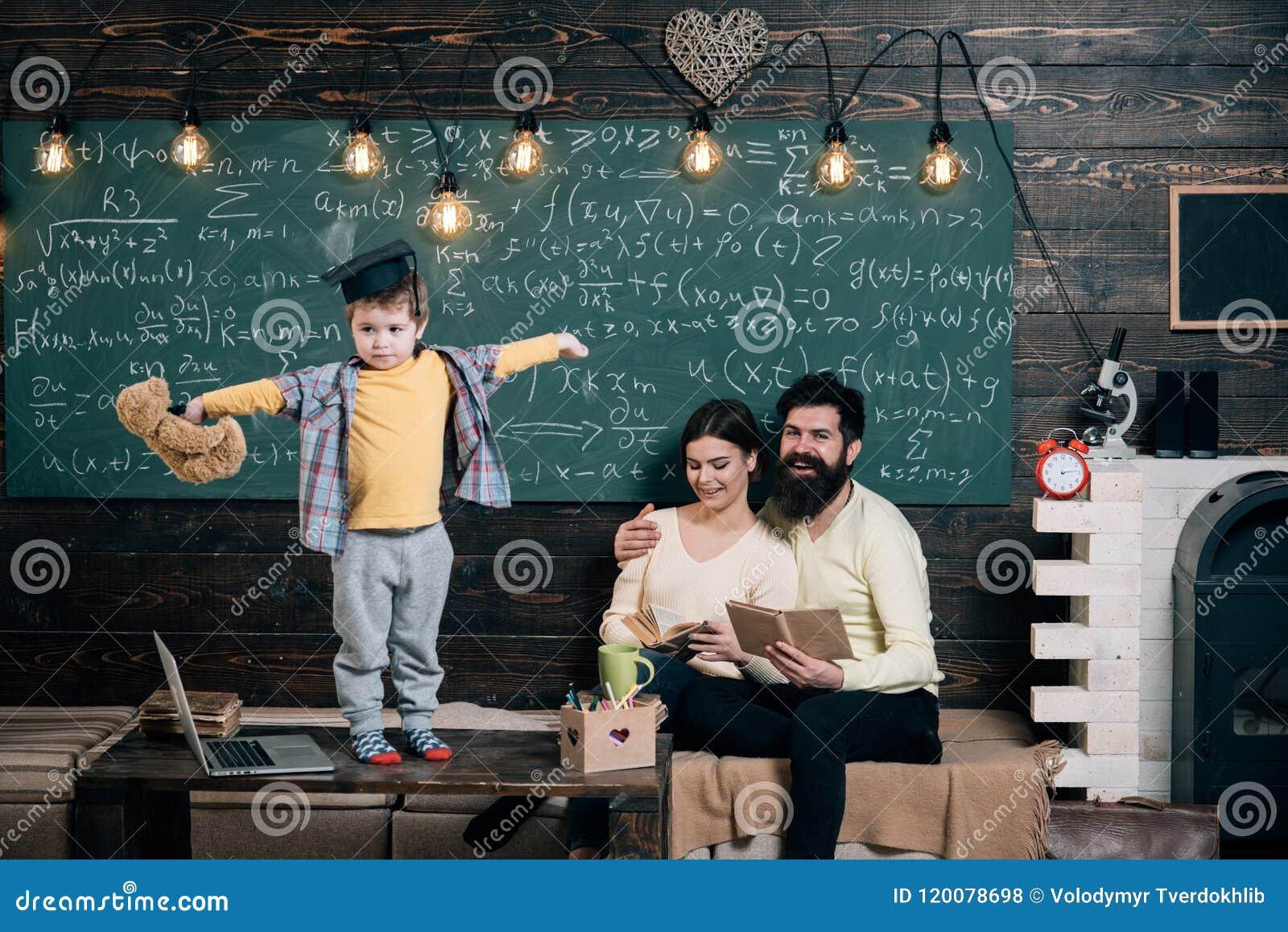 Concepto de la ayuda El niño celebra el oso y la ejecución de peluche Muchacho que presenta su conocimiento a la mamá y al papá P
