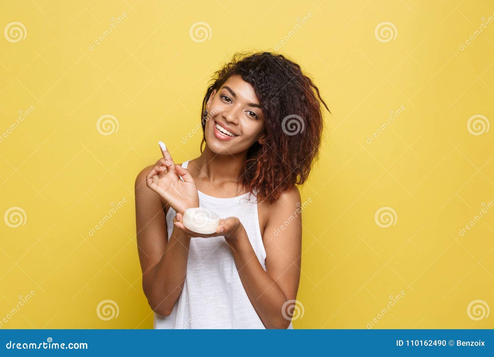 Concepto de la belleza - mujer afroamericana joven hermosa feliz usando la crema del cuidado de piel Fondo amarillo del estudio c