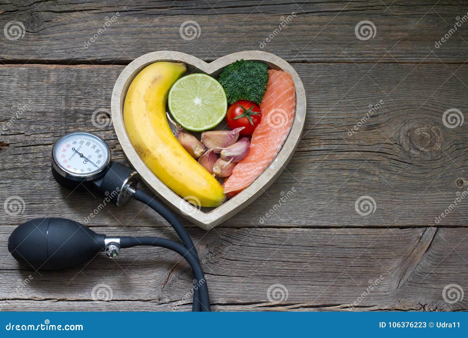 Concepto de la comida de la dieta del corazón de la salud con el indicador de la presión arterial