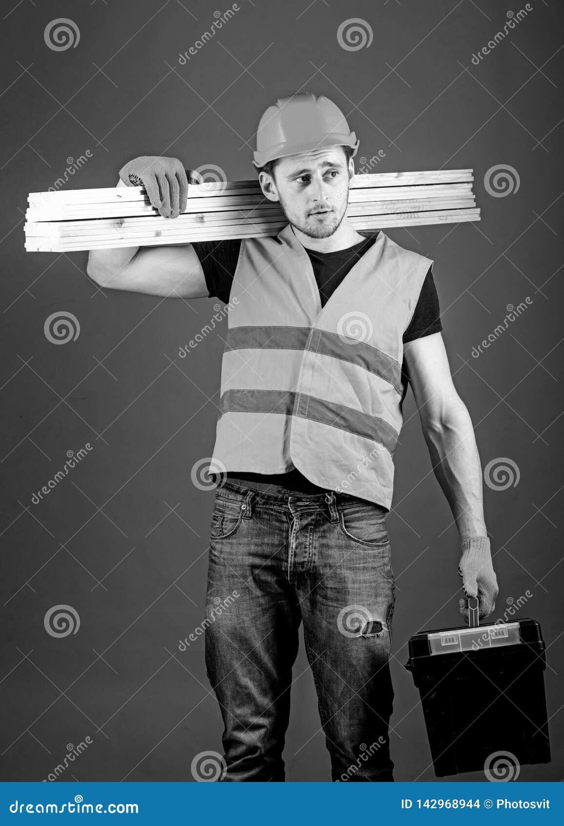 Concepto de la construcción y de la carpintería El carpintero, carpintero, trabajador, constructor en cara soñadora lleva haces d