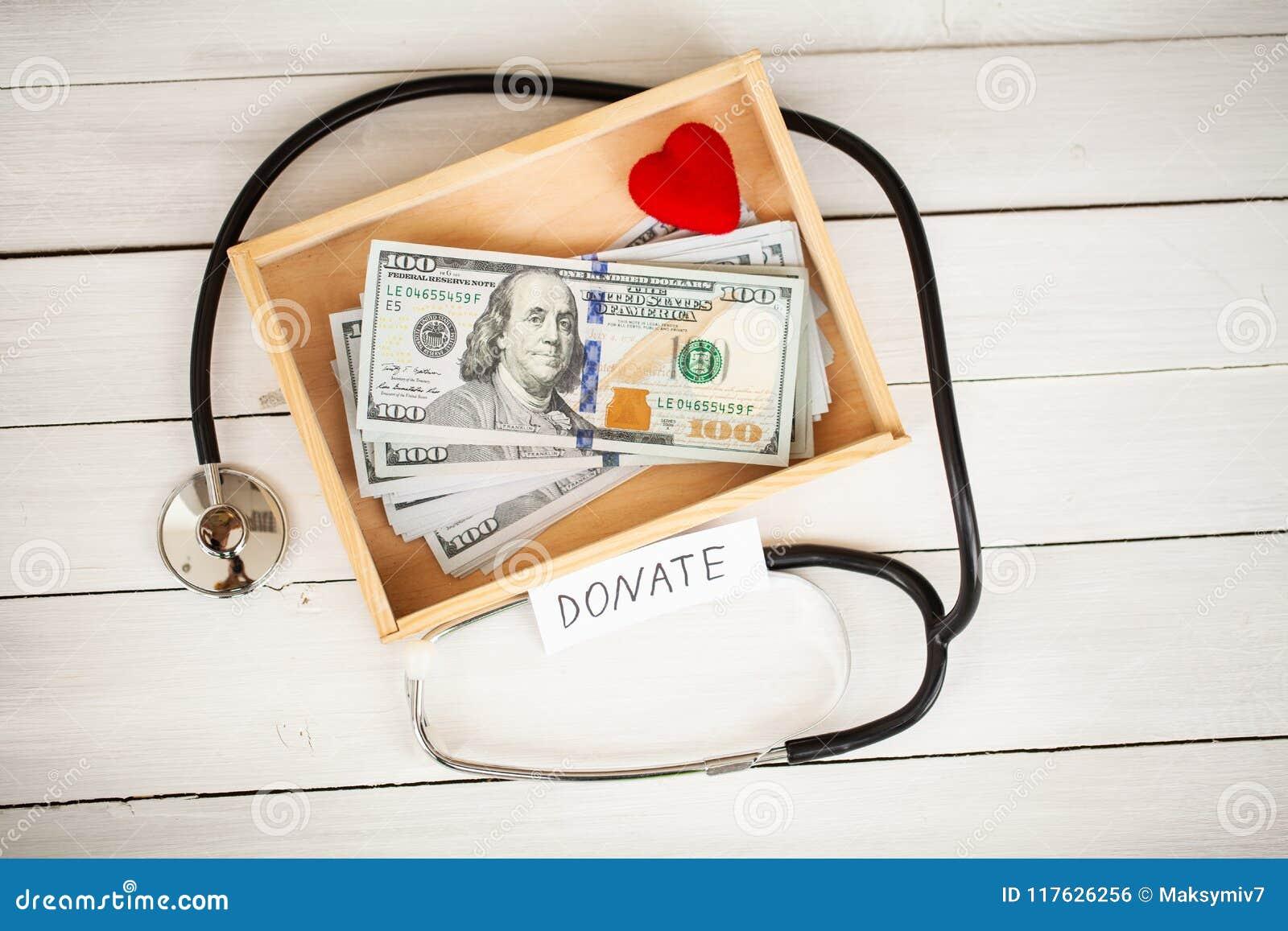Concepto de la donación Caja con los dólares en el fondo blanco donaciones De alta resolución