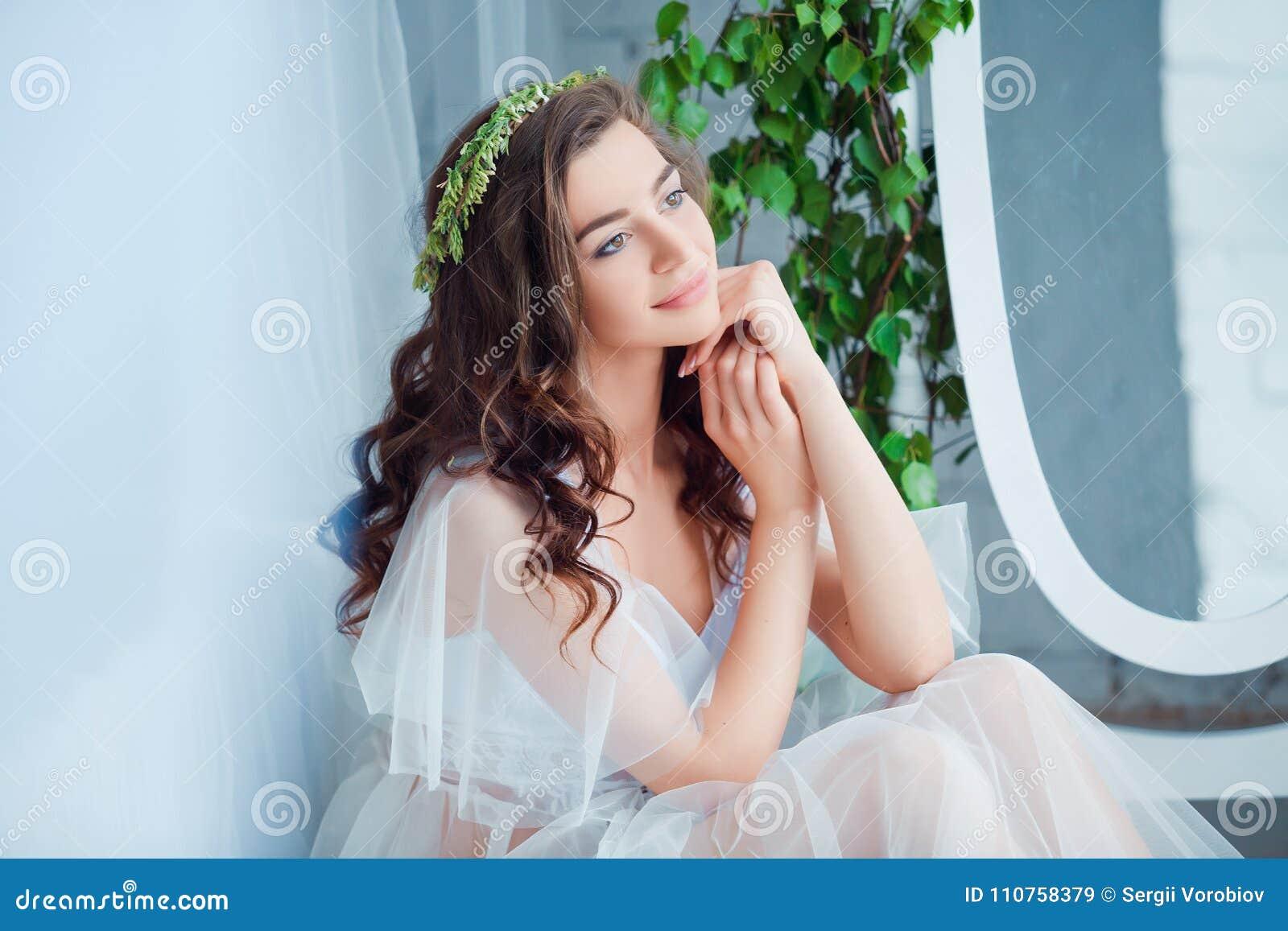 Concepto de la dulzura y de la sensualidad Modelo moreno hermoso que presenta en cama en la ropa interior blanca Retrato sensual
