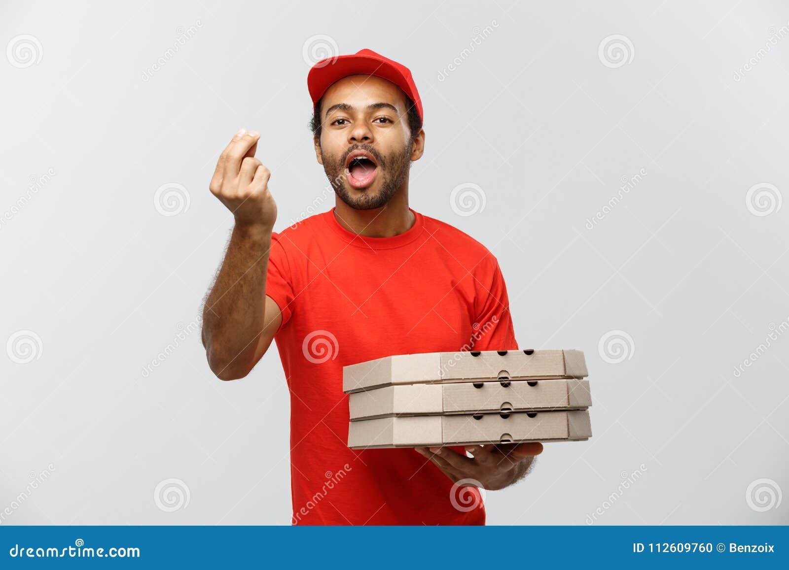 Concepto de la entrega - retrato del hombre de entrega afroamericano feliz que muestra gesto delicioso a mano con sostener las ca