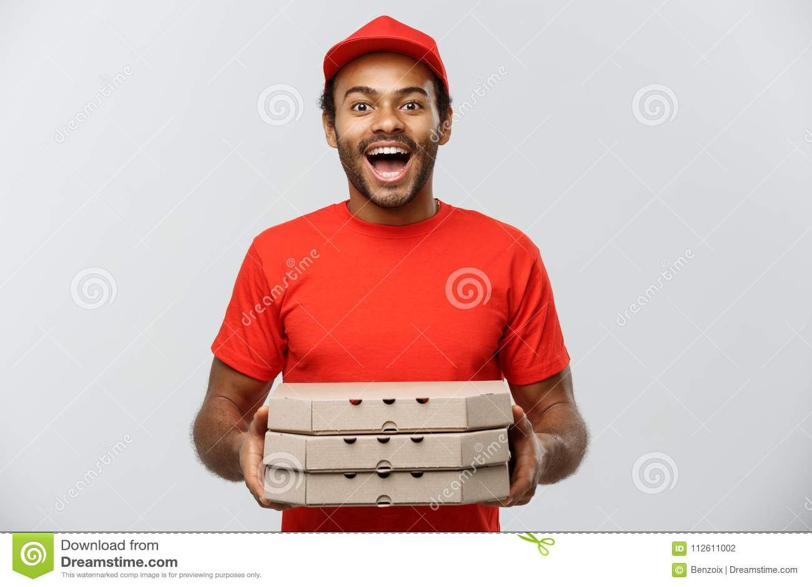 Concepto de la entrega - retrato del hombre de entrega afroamericano hermoso de la pizza Aislado en fondo gris del estudio copia