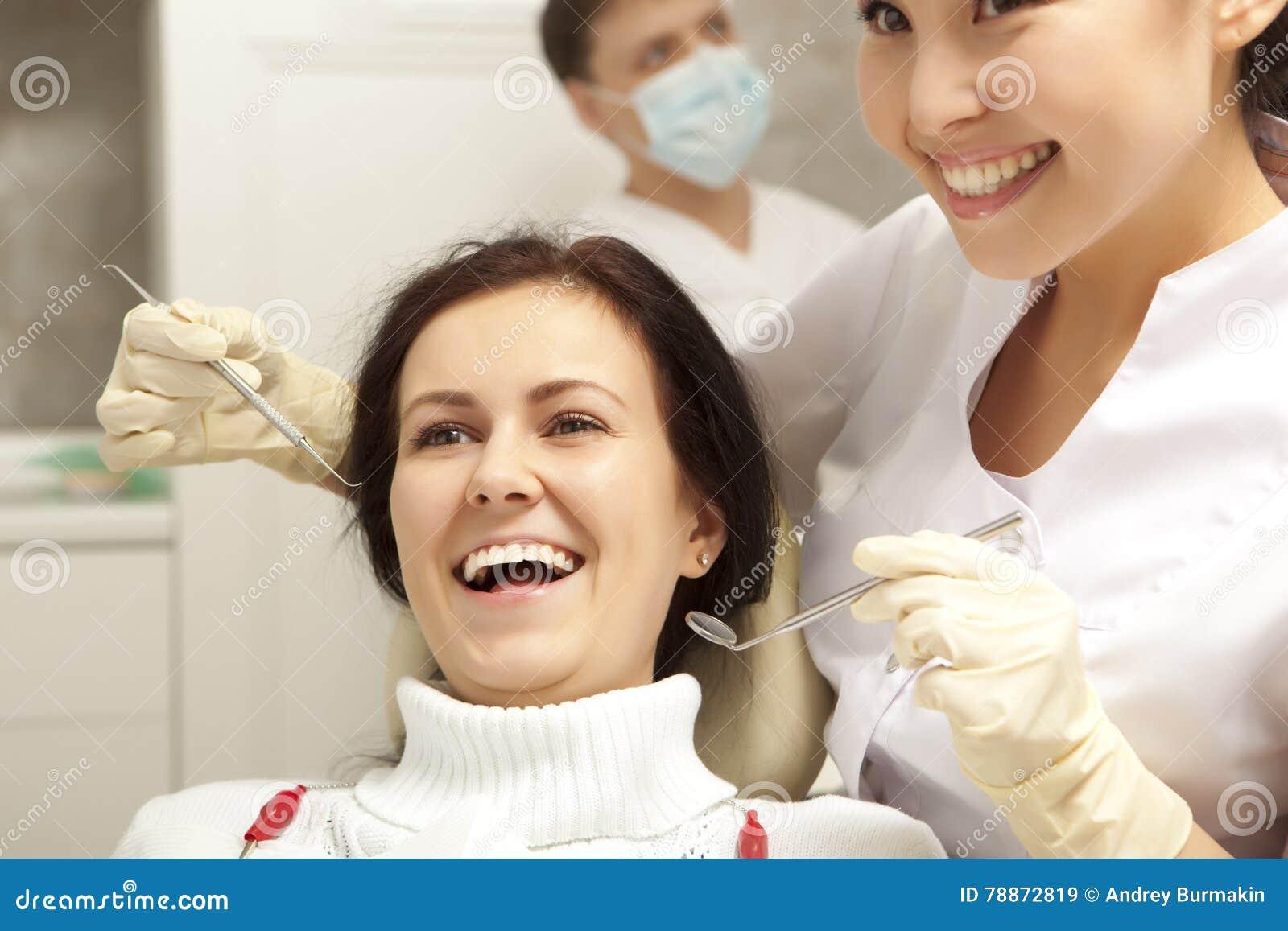 Concepto de la estomatología - dentista con el espejo que comprueba a la muchacha paciente