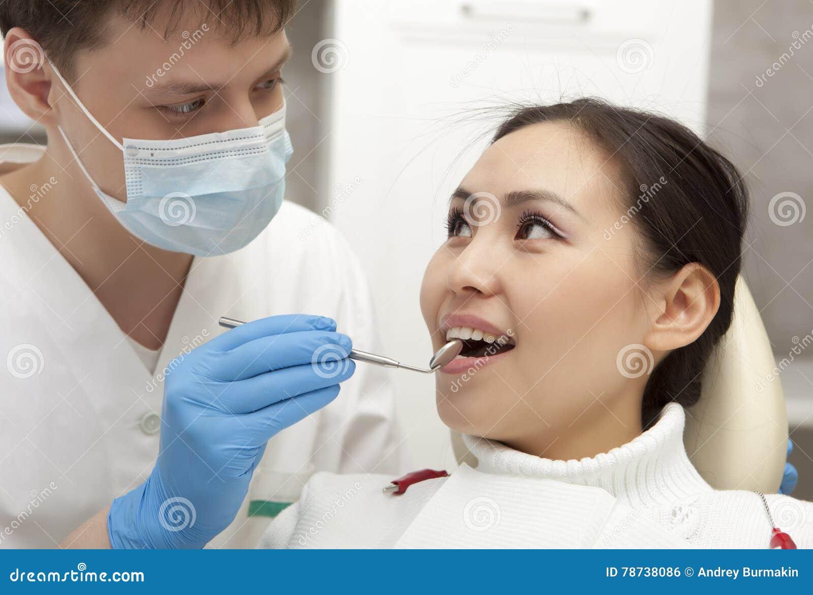 Concepto de la estomatología - dentista de sexo masculino con el espejo que comprueba al paciente