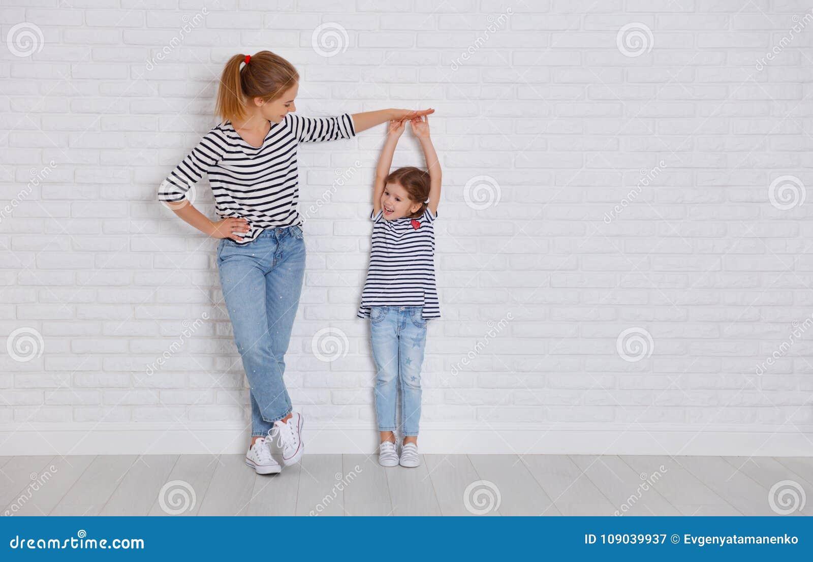 Concepto de la familia la madre mide el crecimiento del niño al daught